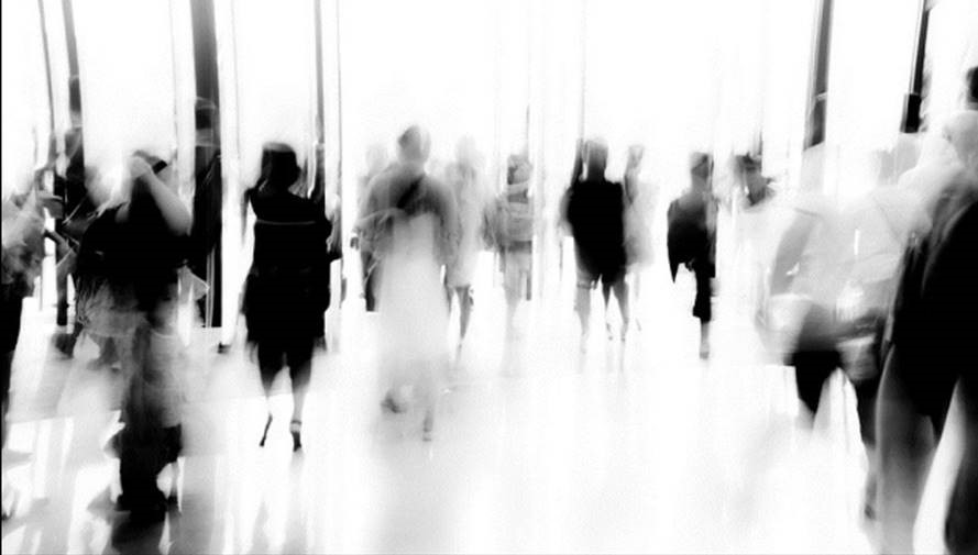 Black-and-white long exposure of people walking through a hallway. People are blurred, and no one is fully distinguishable.